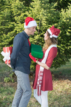 exchanging: Happy young couple exchanging Christmas presents outdoors Stock Photo