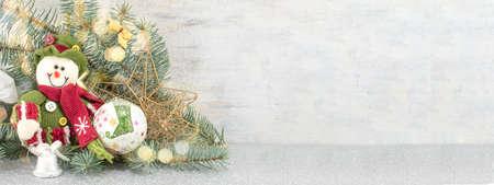 Dressed up snowman under a Christmas lit fir branch 写真素材