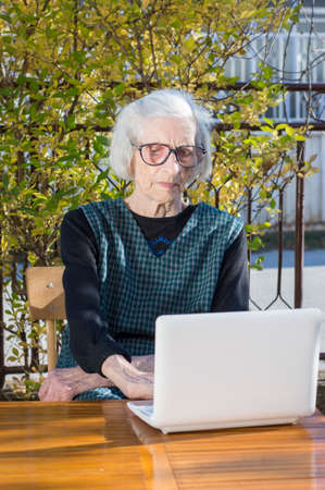 video call: 90 years old woman having a video call on a white notebook Stock Photo