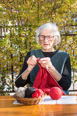 80 90: 90 years old woman knitting a red sweater outdoors