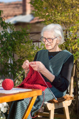 90 years old woman knitting a red sweater outdoors