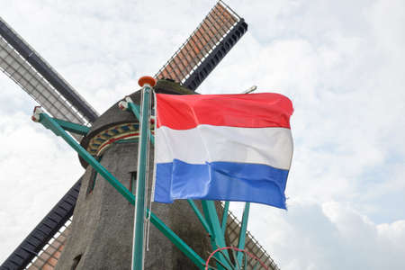 Dutch flag on a windy day in front of an old  windmill