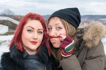 mischevious: two girls having fun in the winter weather, one girl is making a mustache with her hair