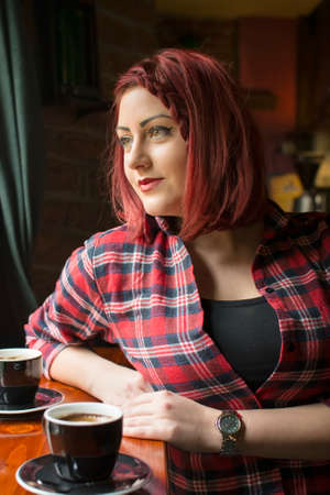 plaid shirt: redhead girl in a plaid shirt at a coffee shop looking at the window Stock Photo