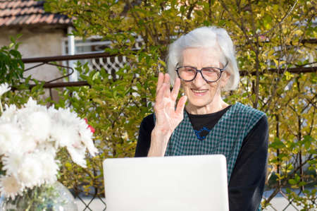 video call: 90 years old woman waving while having a a video call on a white notebook