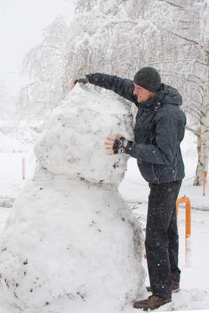 tall man: Tall man making really tall snowman while massive snow storm