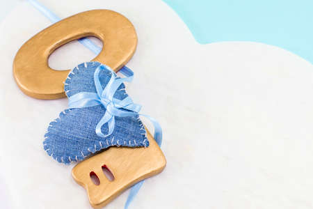 unchain: denim heart wrapped around a big wooden key against a cloud design