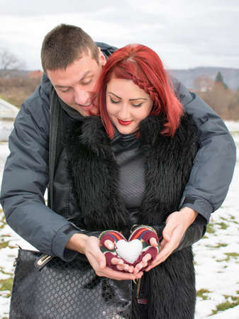 cool people: Happy couple holding a snow shaped heart outdoors