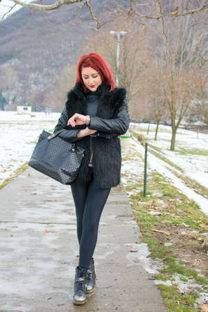 winters: Redhead girl checking her watch on a winters day outdoors