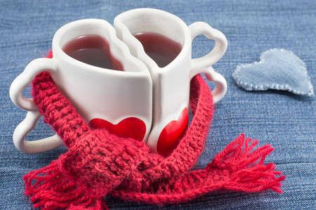 denim background: heart shaped mug with tea on denim background] Stock Photo