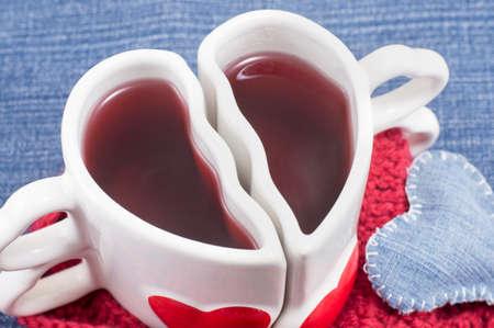 denim background: heart shaped mug with tea on denim background