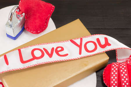 wrapped gift: wrapped gift and I love you ribbon on top of it with hearts
