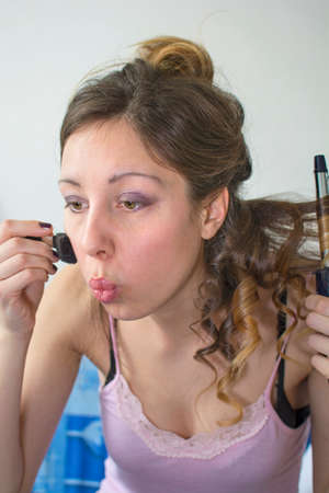 Girl straightening her hair and putting on makeup indoors Фото со стока
