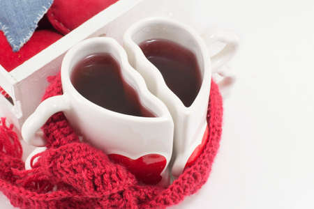 red scarf: heart shaped mug with tea with a red scarf