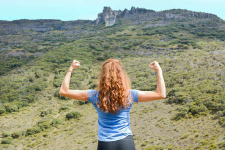 girl in a blue tee shirt flexing muscles on a mountaintop Stock Photo
