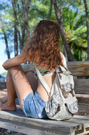 mid twenties: brunette sitting on a park bench in summer with her back to the camera