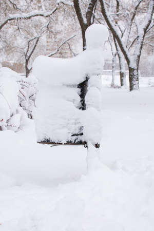 public waste: Snow covered modern trash can in the park