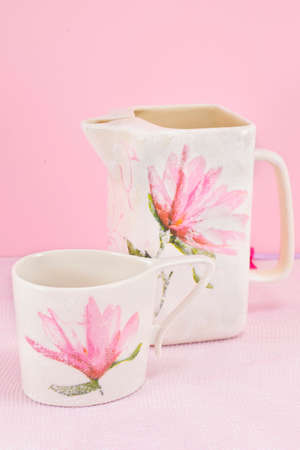 refurbish: Decoupage decorated tea pot and tea cup against pink background