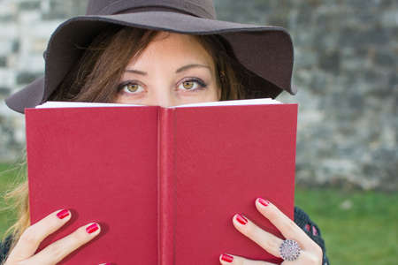 red book: Brunette girl holding a red book while wearing hat Stock Photo