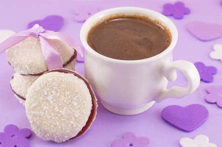 flor morada: Blanco taza de caf� con el postre en una mesa decorada de color p�rpura Foto de archivo
