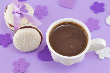 purple hearts: White cup of coffee with dessert on a purple decorated table Stock Photo