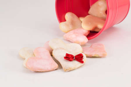 falling out: Heart shaped cookies falling out of the red bucket