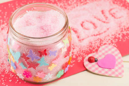 red pink: Bath salt in a jar next to a pink plaid heart symbol Stock Photo