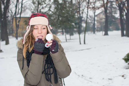 protective: girl putting on makeup outdoors in the snow Stock Photo
