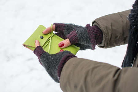 empties: female holding green cellphone case outdoors in the winter