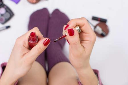 teen legs: Girl applying nail polish while in bed