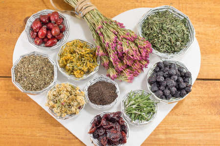 raw tea: bunches of various raw herbal tea in a heart shape Stock Photo