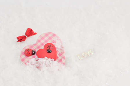 kind hearted: heart with ladybugs in fake snow Stock Photo