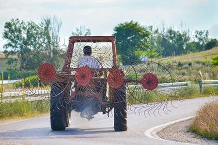 gatherer: tractor with a hay gatherer on the road Stock Photo