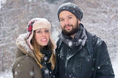 winter park: Bearded boy and brunetet girl posing in the snow