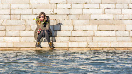 far away look: girl sitting at the river bank at the other side of the river Stock Photo