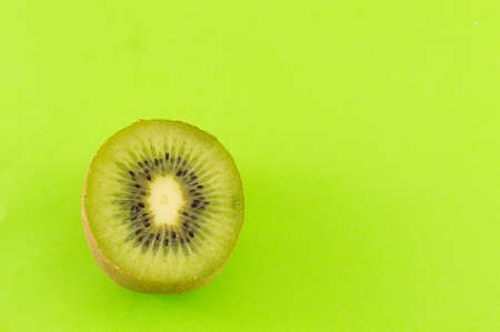 green and white: Sliced fresh kiwi on green background