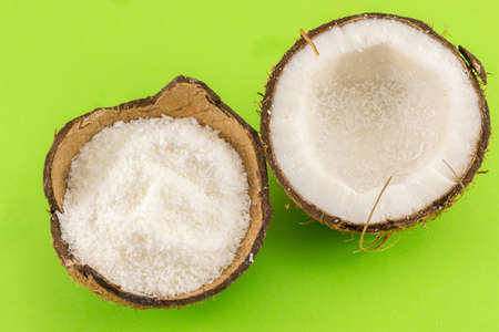 brown background: Coconut powder in coconut shell and fresh coconut on green background