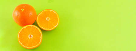 Whole and sliced oranges on green background 写真素材