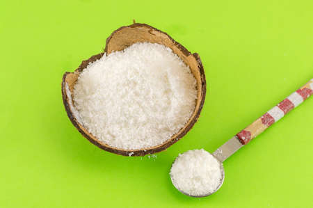 green background: Coconut powder in coconut shell and fresh coconut on green background