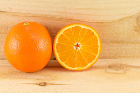 c vitamin: Whole and sliced oranges on green background Stock Photo