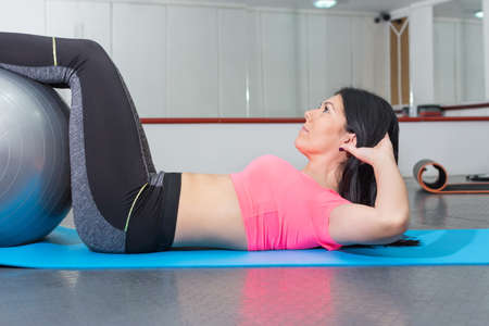 laying abs exercise: Attractive young woman doing crunches with pilates ball at the gym