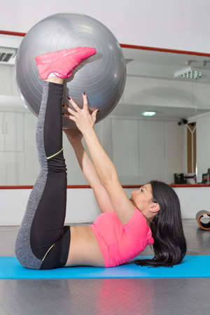 laying abs exercise: Attractive young woman doing crunches with pilates ball