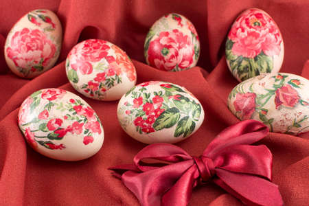 soft background: Colorful decoupage decorated Easter eggs on soft red fabric