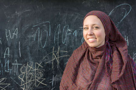 girl studying: Happy woman teacher in hijab in front of the blackboard