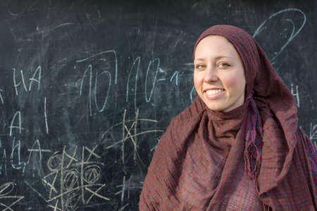 fille arabe: professeur de femme heureuse en hijab devant le tableau noir Banque d'images