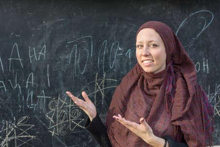 arab adult: Happy woman teacher in hijab in front of the blackboard