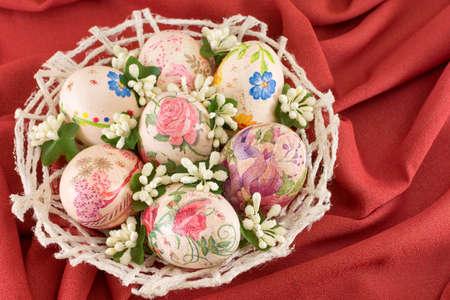 fondo rojo: decoupage colorido decorado huevos de Pascua en una cesta con fondo rojo sof