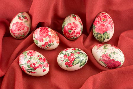 silk background: Colorful decoupage decorated Easter eggs on soft red fabric