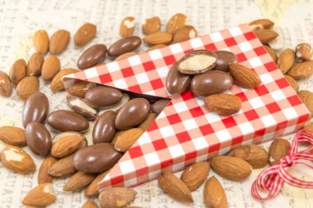 falling out: Fresh and chocolate covered almonds falling out of decorated box
