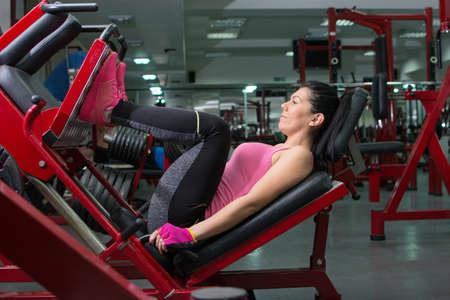 femme brune sexy: Brunette faire la presse jambe dans le gymnase Banque d'images